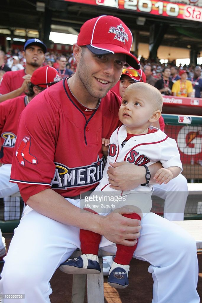 Dustin Pedroia #15 of the Boston Red Sox with his son during the 2010 State Farm Home Run Derby at Angel Stadium of Anaheim on July 12, 2010 in Anaheim, California.