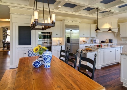 Love the layout of this kitchen...the island in the middle, the long kitchen table, corner stove, double ovens, and lets not forget the gorgeous floors.