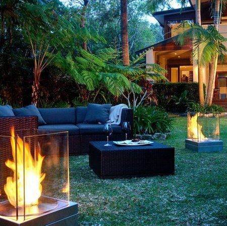 Contemporary Garden With Elegant Tiki Torches