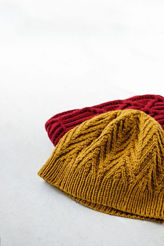 A cabled beanie at two different scales gives you gift-knitting options for the whole family. A single-rib brim feeds cabled spires with deep chevrons of traveling stitches that culminate in a perfect five-pointed star at the crown. Work in Quarry for a warm and quick-knitting cap with deep, soft texture or choose Arbor for vivid definition and a more ornate effect.