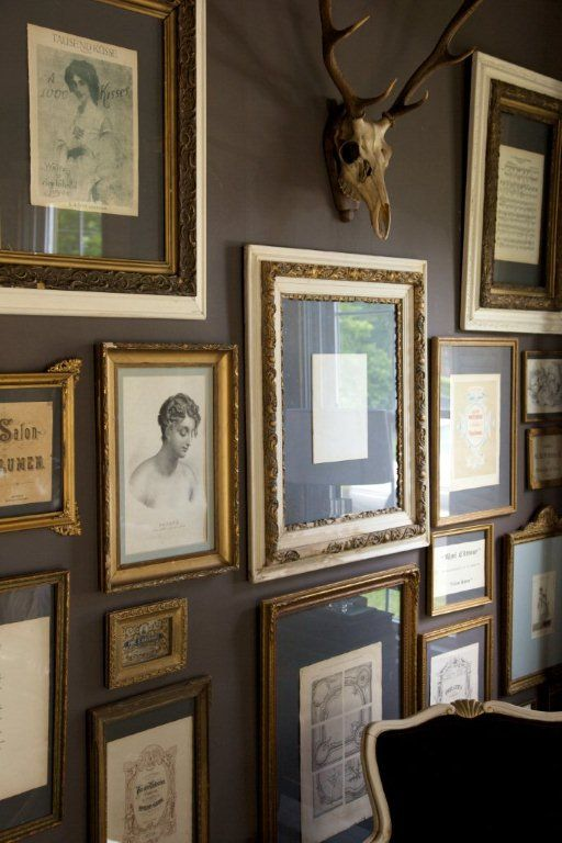 love the white and gold frames against that darker color on the wall!