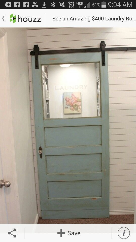 Old, exterior door repurposed as barn door laundry room
