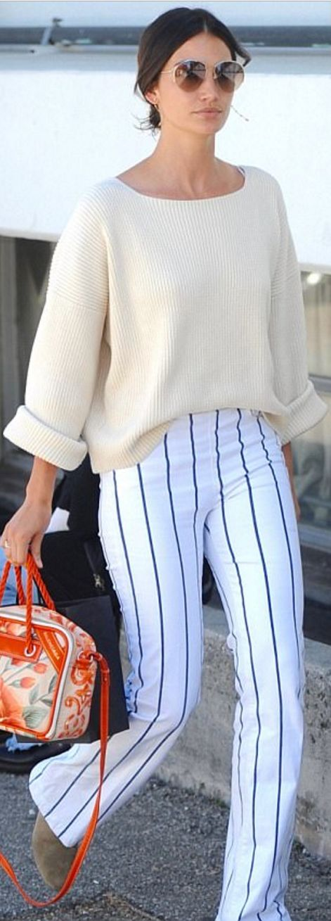 Who made Lily Aldridge's jewelry, brown suede ankle boots, sunglasses, orange floral handbag, white striped pants, and tan ribbed sweater?