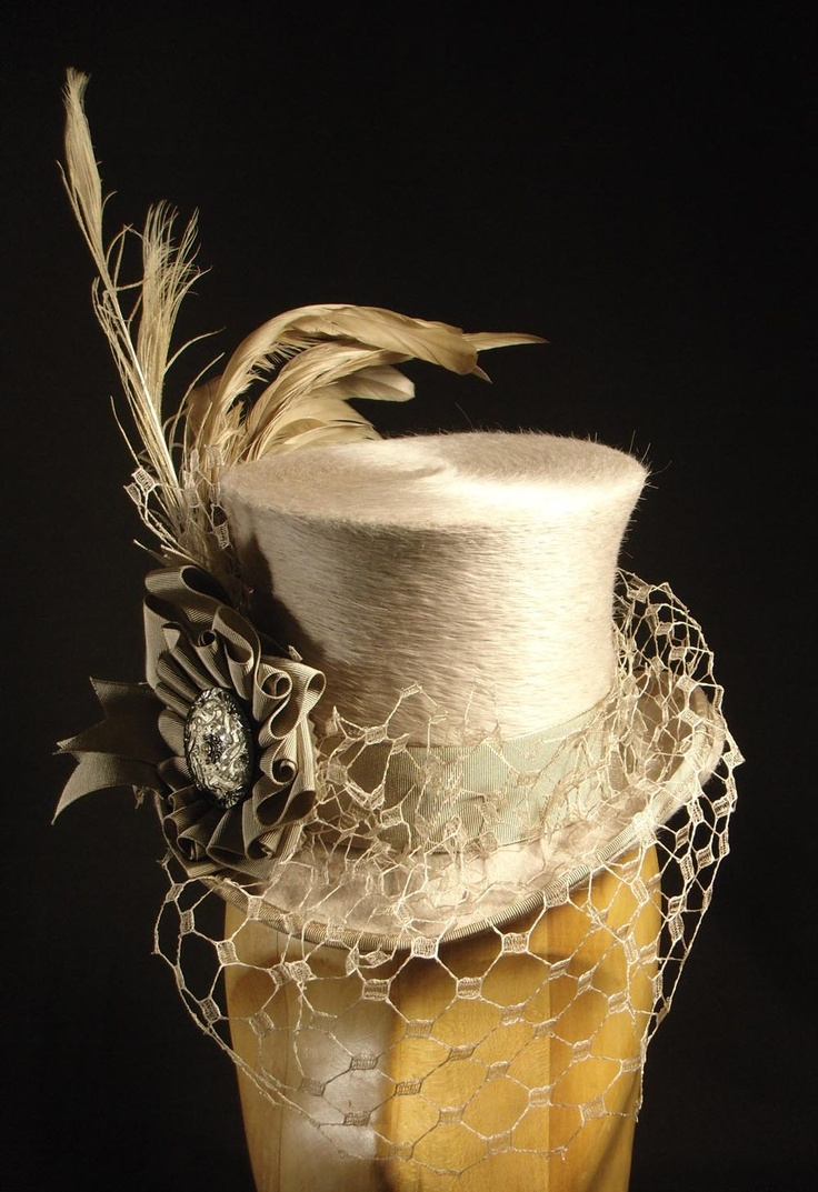 A 'Belle Epoch' mini top hat in alabaster beaver felt, with bleached peacock and coque feathers, and matching veiling