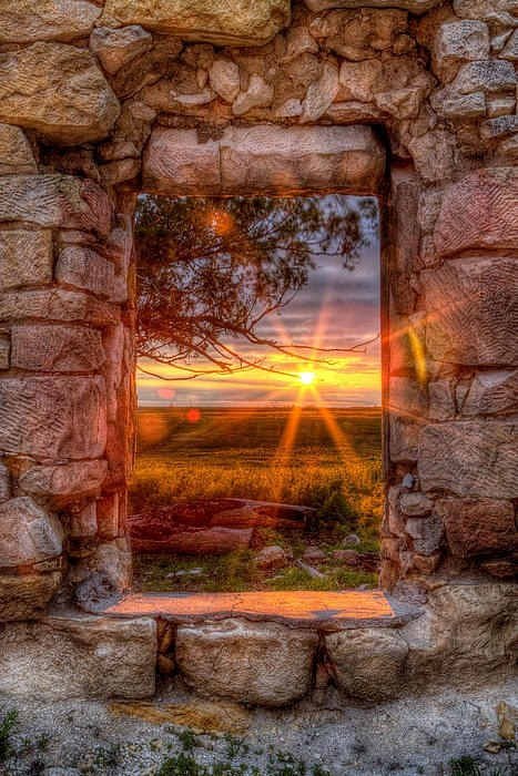 """The photographer describes it this way... """"A Kansas sunset through the window of an abandoned and forgotten limestone house in Ellis County. This was a bedroom window, and you have to wonder how many sunsets were watched by the family who built and lived in the house originally."""" Simply beautiful! ~"""