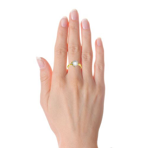 Versatile ring blessed with purity of fresh water button pearls crafted in 18k yellow gold. This feminine beauty is decorated with sparkling diamonds in the edge.