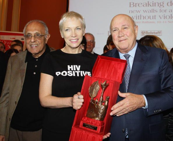 Former South African leader Frederik Willem de Klerk hands over the Peace award to musician Annie Lennox as Ahmed Mohamed Kathrada smiles on the...