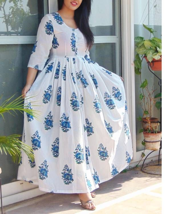 Blue block printed cape    White coloured cape with blue hand block print. This floor length tunic has buttons in the front for closure and a round neckline. Team it with a statement neckpiece to add to the glamour.