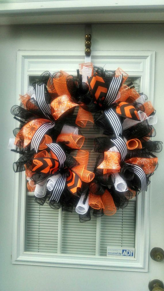 This is a Halloween wreath. It is made with orange white and black deco mesh. I used orange and black chevron, black and white stripes and