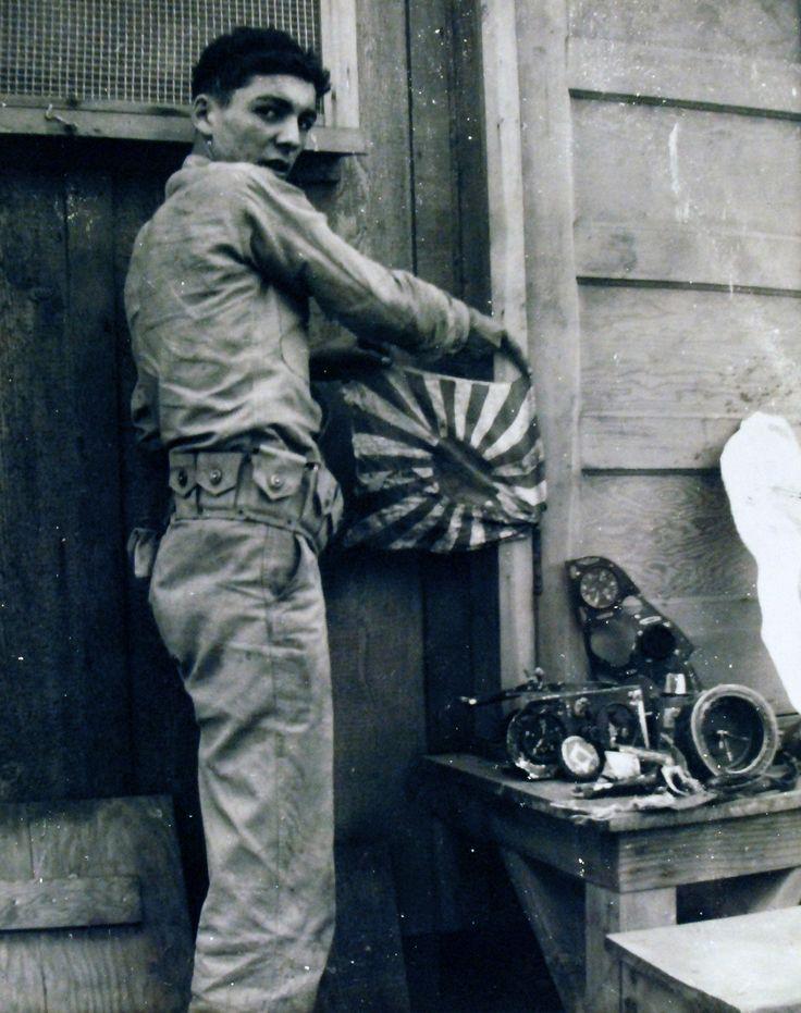 """80G-32780: épave de l'équipement japonais capturé à Pearl Harbor, Territoire de Hawaii, le 7 Décembre 1941. Avion carte du panneau équipement d'un type Navy 99 Transporteur Bomber japonais, un D3A Aichi """"VAL"""". Sailor tenant japonais Naval Ensign."""