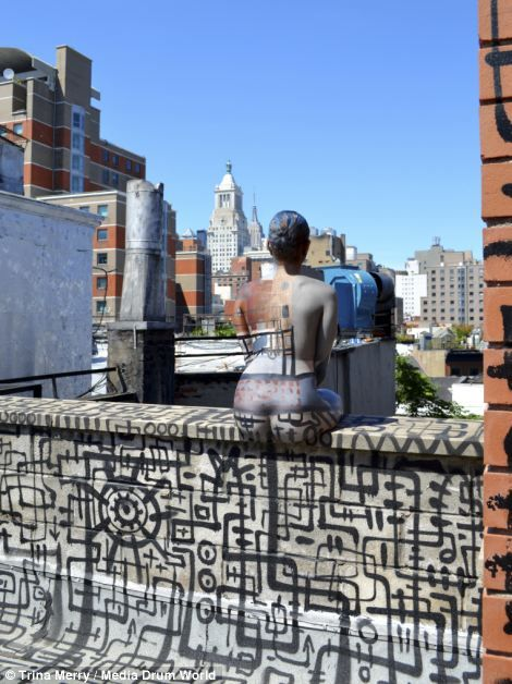 A body painted model sits with her back to the camera gazing out across the city...