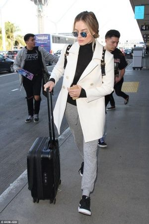 Margot Robbie wearing Victorinox Spectra Dual-Access Extra Capacity Carry on Luggage, Burberry the Rucksack in Technical Nylon and Leather, Puma Suede Classic Trainers and Ray-Ban Round Sunglasses