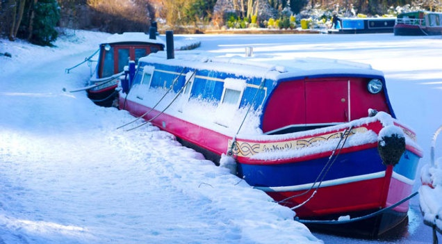CANAL NARROW BOATS | moored narrowboat covered in snow