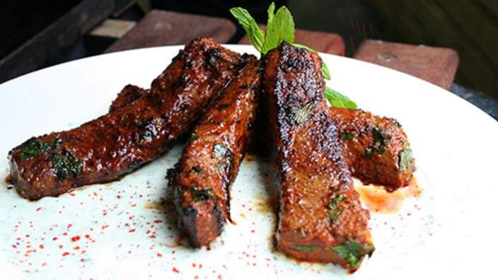 Barbecued lamb (mechoui) with minted yoghurt | Here is a dead-easy Moroccan marinade recipe for lamb that is full of incredible flavour. The cool taste of mint and the tang of yoghurt team beautifully with the barbecued meat. As well as lamb backstraps or fillets, you can try this with chops.