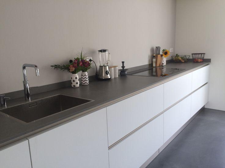 Moderne keuken strakke keuken witte keuken blad is betonlook dun aanrechtblad quooker vloer is woonbeton muur is grijs renovlies met coating