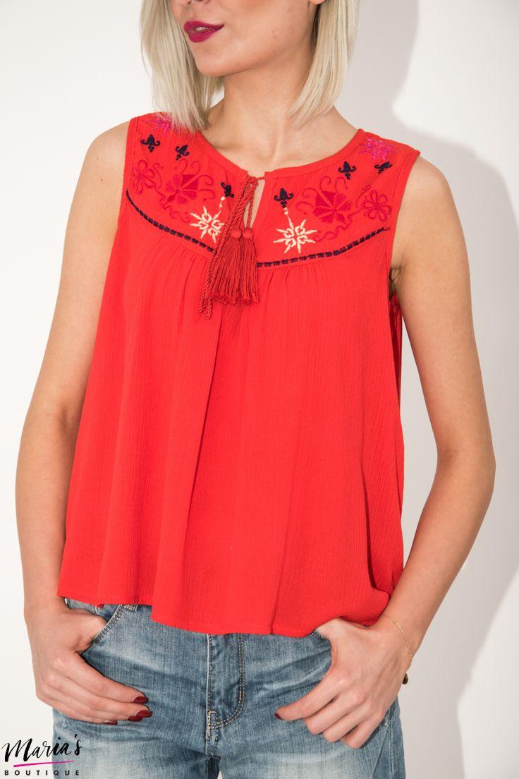 Bluză din material 100% vâscoză, de culoare roșie cu decolteu rotund. Este accesorizată la baza gâtului și în zona bustului cu elemente brodate și șnur cu canafi. Terminația este simetrică, dreaptă.