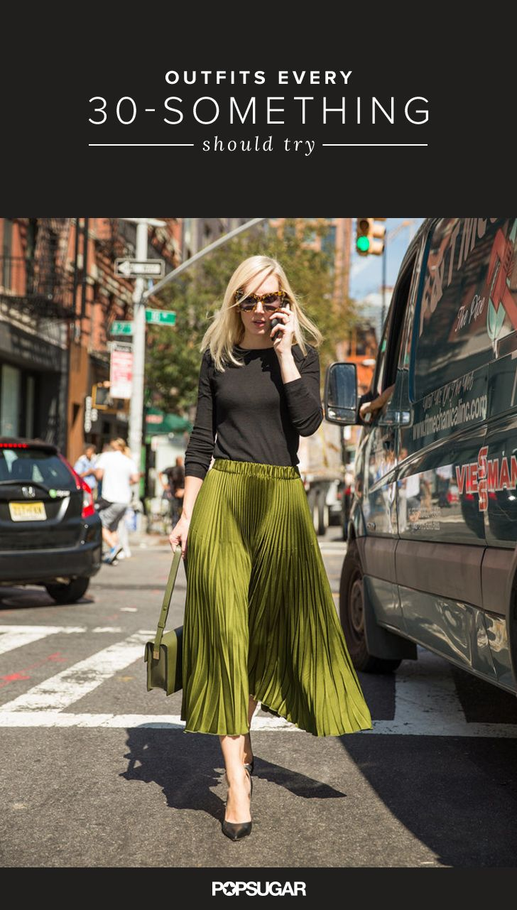 A green pleated skirt, black shirt, and olive purse