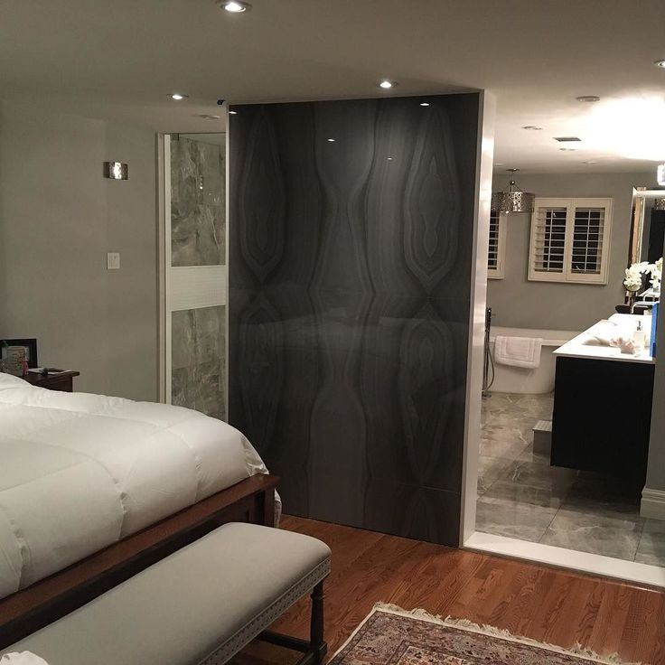 Recently completed #MarbleTrend project - Converted a fireplace wall to a feature wall using bookmatched Absolute Deep porcelain separating the master bedroom from the master bathroom.