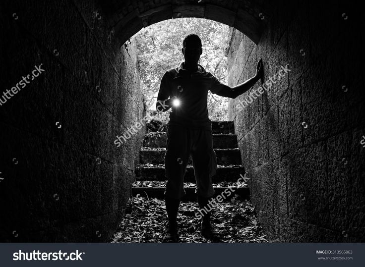 Young Man With A Flashlight Enters The Stone Tunnel And Looks In The Dark, Monochrome Photo - 313565063 : Shutterstock