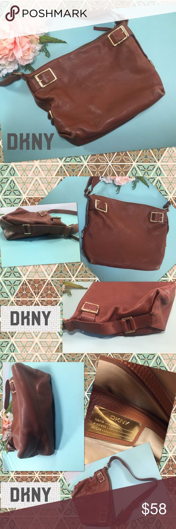 DKNY Brown Pebbled Leather Bucket Bag DKNY Brown Pebbled Leather Bucket Bag has gold tone hardware, buckle detailing, high-quality pebbled leather, Long adjustable shoulder strap, light tan interior with one zip pocket, and a few other utility pockets. As seen in photos, there is moderate wear on base corners, but the bag still looks very nice. Interior lining shows signs of usage. Medium sized bag. Orig. $198. Dkny Bags Shoulder Bags