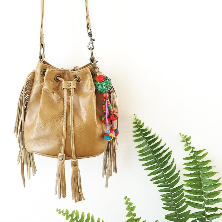 Handcrafted leather fringed bucket bag with gypsy tassel pompoms by Amber Gaye