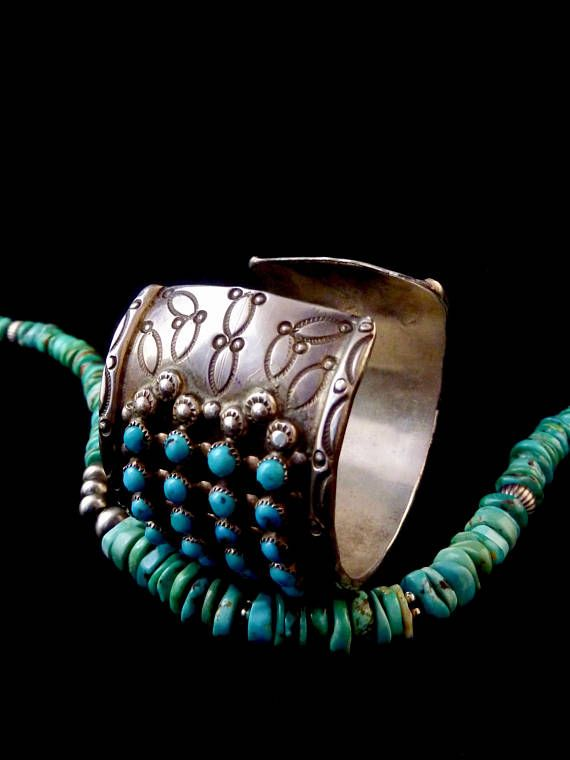 This is an AWESOME vintage Navajo sterling silver cuff featuring 4 rows of masterfully hand-cut, BRIGHT BLUE Kingman turquoise snake-eye stones!  Kingman, Arizona is home to the famous Kingman Turquoise Mine. The city of Kingman itself predates Arizona's statehood. When it was founded in 1882, there was little more than a railroad siding, a temporary store, a hotel and saloon.  The Kingman Turquoise Mine and was first discovered and mined by ancient Native American civilizations long before…