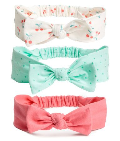 White/cherry. Jersey headbands with an attached bow at front and elastication at back.