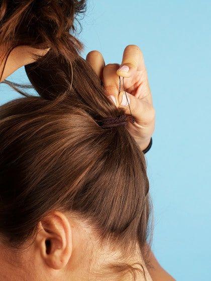 Haarnadel hinter dem Zopf waagerecht in den Haargummi klemmen