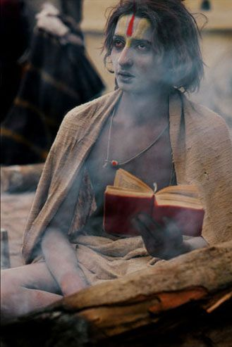 A young sadhu reads holy scripture near the fire