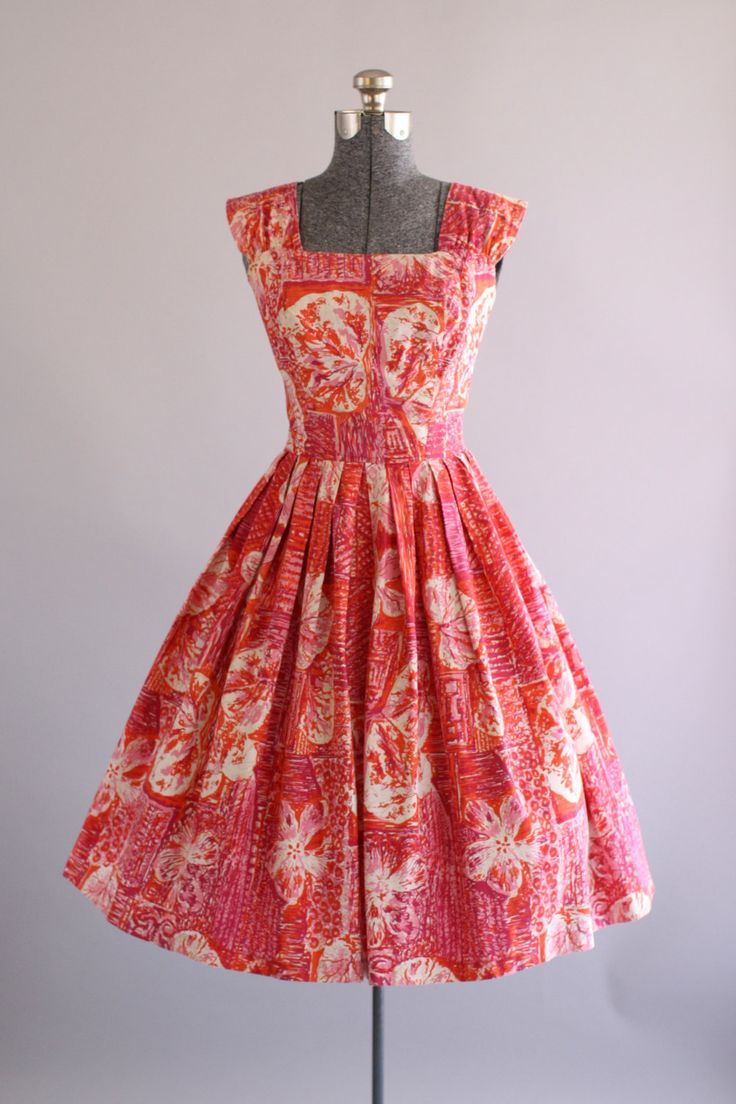 This 1950s Made in Hawaii cotton dress features an amazing atomic hibiscus floral print in shades of red, fuchsia and orange. Square neckline.