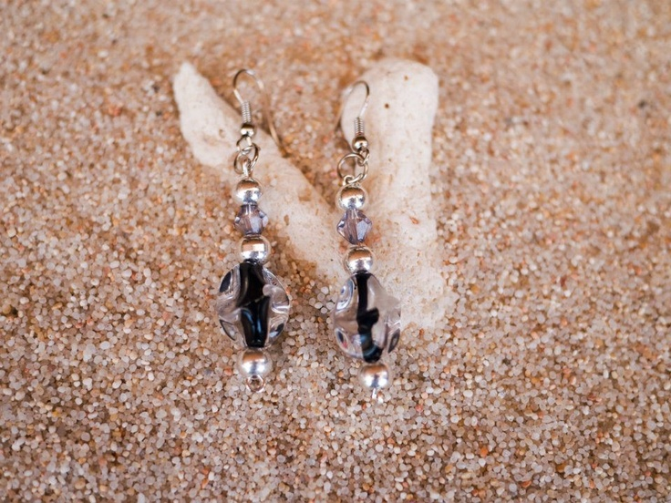 Pendientes con bolitas de plata y adornos transparentes con el interior negro.
