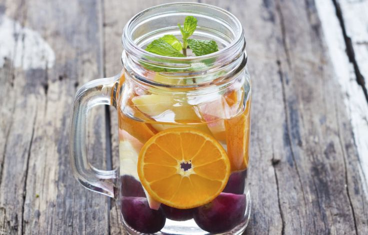mug delicious refreshing drink of mix fruits with mint on wooden, infusioned water