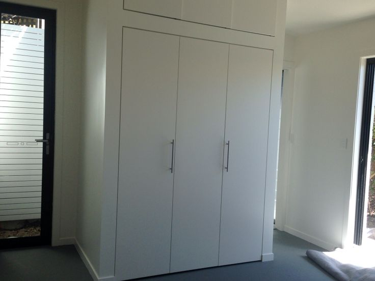 Kitchenette and washing machine behind bifold doors.  My latest project! A granny flat / home studio / teenager retreat in Bondi Beach. Enclosed kitchenette.