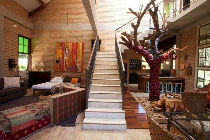 A rusticidade desta casa de 350 m em Campos do Jordão reflete o espírito desprendido de seus donos que cultivam a arte de morar sem excessos. Dentro do pátio interno uma árvore com 6 metros de altura foi mantida. A casa foi construída em volta dela. A escada paralela à árvore foi revestida de pó de mármore branco com um corrimão de ferro. O lustre pendurado na árvore é de acrílico trazido de Milão.  #projetoevelinsayar #olhomagicocj #casaejardim #decoracao #arquitetura #instadecor #design…