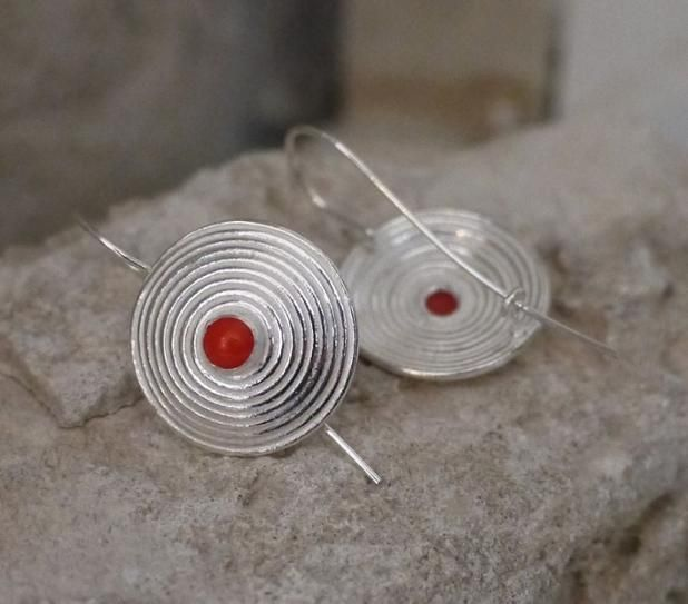 Silver swirl earrings with coral   This fantastic pair of silver earrings are so much fun to wear, fully handmade and a unique addition to our Seba Silver collection. The earrings are gently curved to a central coral bead that has been shaped to exactly fit in the center of the earrings.  The solid silver hooks are attached at the top & centre of each earring and loop safely into a hook at the base of the earrings – as seen in the image above.  The earrings have a diameter of 20mm and the…