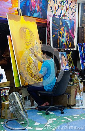 Thailand: painter paints a picture in a indoor studio
