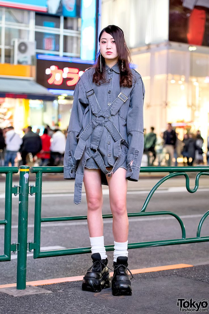 Her look here features a gray harness shirt by the Japanese streetwear brand MYOB NYC with vintage shorts, loose socks, and tall Demonia platforms.