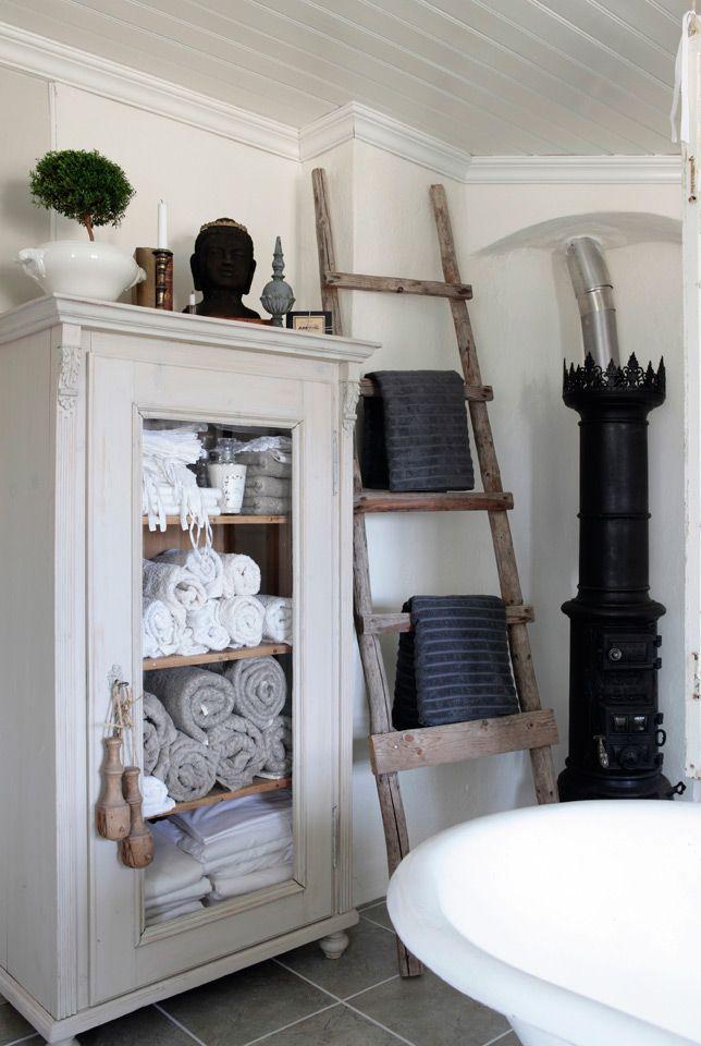 I det gamle, antikke skapet oppbevares håndklær. Den gamle stigen brukes som håndklehenger.