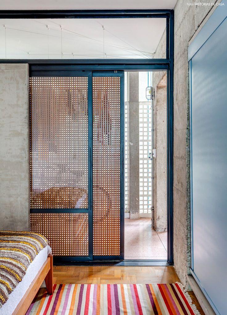 porta de correr de muxarabi, tapete listrado e paredes de concreto em um quarto no Copan, em SP