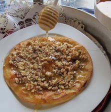 Ακροβατεί μεταξύ πίτας και κρέπας. Είναι τόσο λεπτή που κάποιος απορεί πως μπορεί να έχει με τόση επιτυχία απλωθεί σε ολόκληρη την επιφάνεια της το τυρί. Πάντως είναι πεντανόστιμη και μπορείτε να την απολαύσετε με ή χωρίς μέλι