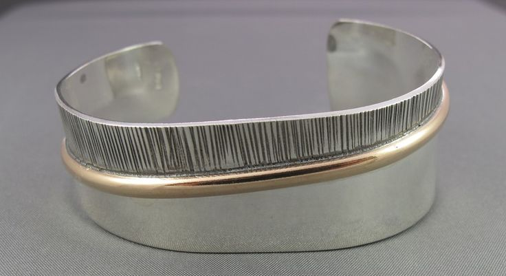 Sterling Silver & 14KT Gold Filled, smooth and textured cuff bracelet. Adjusts to fit most female wrists.