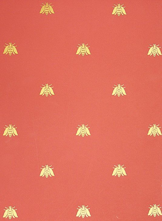 Bee Wallpaper A small gold bee pattern repeat wallpaper on red.