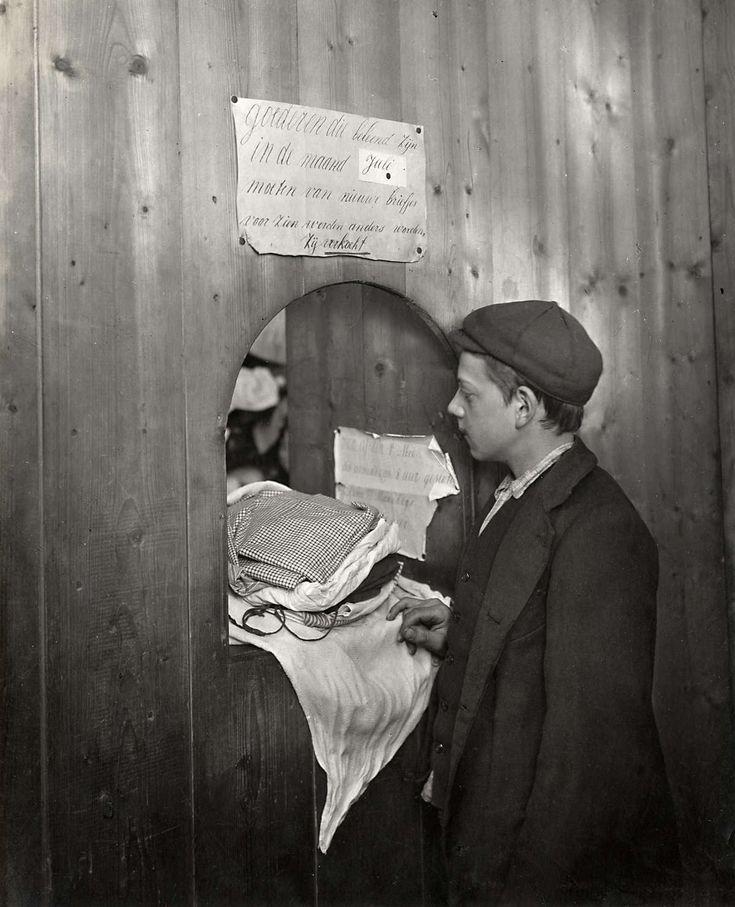 Pandjeshuizen : Jongen beleent textiel bij loket van pandjeshuis. Nederland, Amsterdam, 1913.