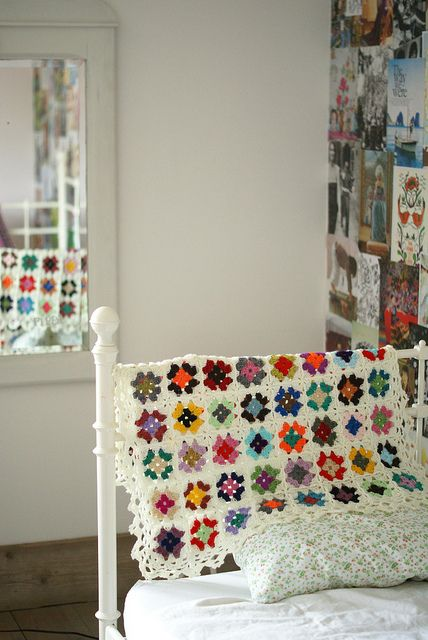 What vibrant colors in this crochet blanket/afghan tossed over the white iron bed frame.