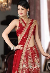 This red faux chiffon lehenga style saree is exclusively embellished with resham, zari, stone, beads and cutdana work in form of floral and paisley motif. Matching blouse comes along with this and it can be customized upto 38 inches. Slight variation in colour is possible.