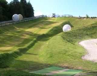 Zorbing. Rotorua. NZ. people are inside of those balls rolling down the hill.