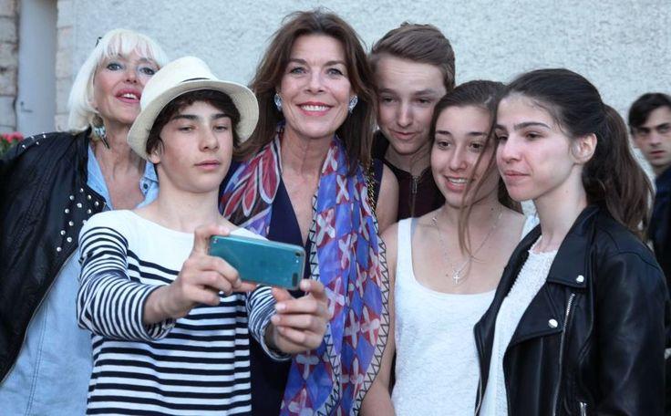 Ziehier een koninklijk generatiekloofje. Terwijl de omstanders zich richten op een zo flatteus mogelijke selfie slaat prinses Caroline van Hanover automatisch aan op de professionele camera.