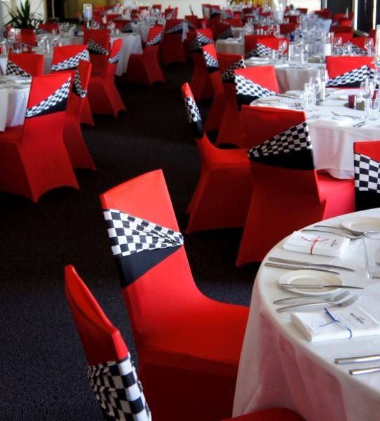 vibrant red chair covers with checker themed bands - table centre to match