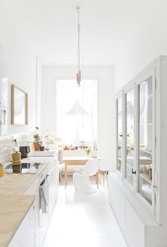 #reforma #cocina de estilo nórdico alargada con muebles blancos, encimera de madera, alacena restaurada, suelo parquet pintado blanco, zona de comedor junto a ventana.