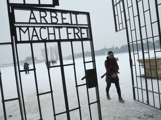 "A visitor walks past an inscription that reads, ""Arbeit Macht Frei,"" which means ""Work Leads To Freedom,"" at the gate of Sachsenhausen concentration camp, whose gate and remaining buildings stand as a memorial, on International Holocaust Remembrance Day on Jan. 27 in Oranienburg, Germany. Sachsenhausen operated from 1933 until 1945."